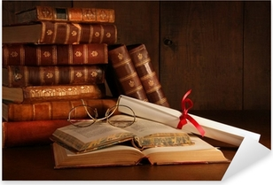 Pile of old books with glasses on desk Pixerstick Sticker