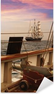 Sticker Pixerstick Pont d'un navire cru au crépuscule avec un voilier à l'horizon