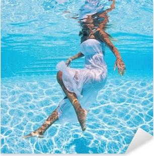 Sticker Pixerstick Portrait de femme sous l'eau avec une robe blanche dans la piscine.