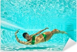 Sticker Pixerstick Portrait de femme sous l'eau en bikini vert dans la piscine.