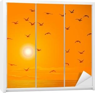 Sticker pour armoire Flying birds contre orange coucher de soleil.