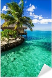 Tropical villa and palm tree next to green lagoon Pixerstick Sticker