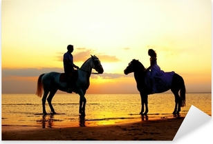 Two riders on horseback at sunset on the beach. Lovers ride hors Pixerstick Sticker