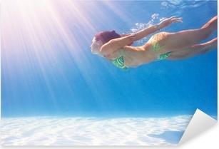 Pixerstick Sticker Vrouw zwemmen onder water in een blauwe zwembad.