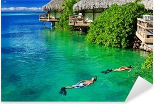 Young couple snorkeling in clean water over reef Pixerstick Sticker