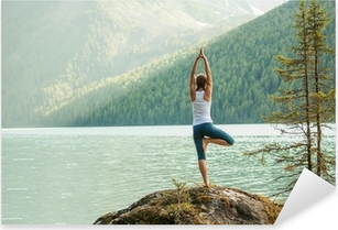 Young woman is practicing yoga at mountain lake Pixerstick Sticker