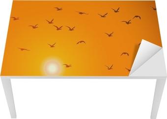 Flying birds against orange sunset. Table & Desk Veneer