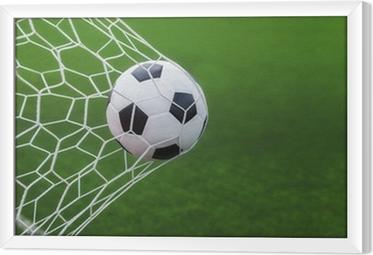 Tableau encadré Ballon de soccer dans les buts avec backgroung vert