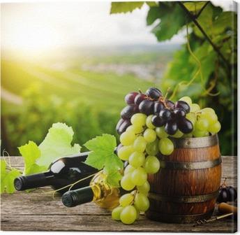 Tableau sur toile Bouteilles de vin rouge et blanc avec des raisins frais