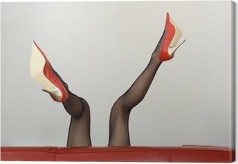 Tableau sur toile Femme sexy dans des talons hauts rouges couché sur un canapé
