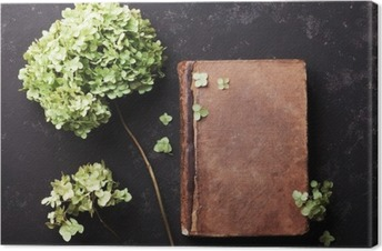 Tableau sur toile Nature morte avec le vieux livre et fleurs séchées hortensia sur noir table vintage vue de dessus. Appartement style laïque.