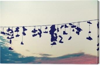 Tableau sur toile Retro stylisé silhouettes de chaussures suspendues sur le câble au coucher du soleil, le concept de rébellion adolescente.