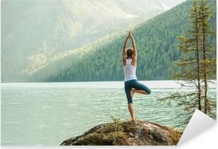 Nuori nainen harjoittaa joogaa vuoristojärvellä Pixerstick tarra