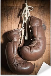 Vanhat nyrkkeilyhanskat, jotka riippuvat puuseinällä Pixerstick tarra