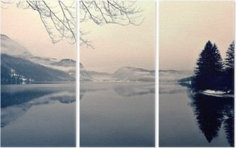Snowy winter landscape on the lake in black and white. Monochrome image filtered in retro, vintage style with soft focus, red filter and some noise; nostalgic concept of winter. Lake Bohinj, Slovenia. Triptych