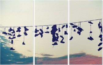 Triptyque Retro stylisé silhouettes de chaussures suspendues sur le câble au coucher du soleil, le concept de rébellion adolescente.