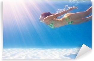 Nainen ui vedenalainen sininen uima-allas. Vinyyli valokuvatapetti