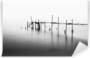 En lang eksponering af en ødelagt pier i midten af havet. Behandlet i B & W. Vaskbare fototapet