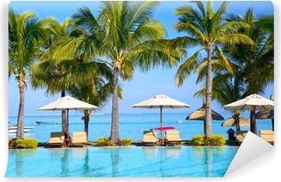 Swimmingpool med paraplyer på stranden i Mauritius Vaskbare fototapet