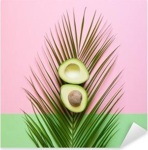 Vinilo Pixerstick Aguacate maduro en hoja de palma en un fondo coloreado. concepto restringido