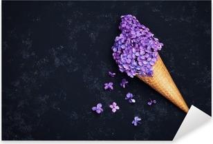 Vinilo Pixerstick El helado de flores de color lila en el cono de galleta sobre fondo negro desde arriba, un hermoso arreglo floral, color de la vendimia, estilo aplanada