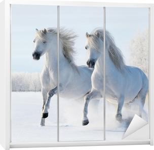 Vinilo para Armario Dos caballos blancos galope en el campo de nieve