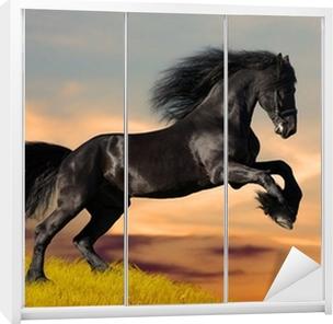 Vinilo para Armario Negro caballo Frisón galopa en la puesta del sol