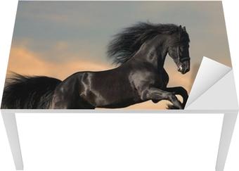 Vinilo para Mesa y Escritorio Negro caballo Frisón galopa en la puesta del sol