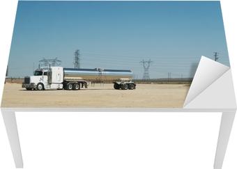 Un camión Semi-remolque con un tanque de gas de cromo por una carretera del desierto