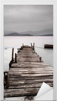 Vinilo para Puerta Mirando sobre un muelle y un barco, baja saturación