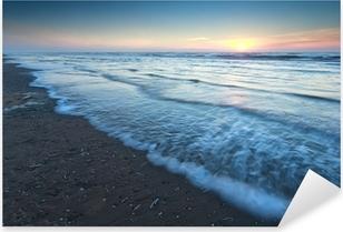 Vinilo Pixerstick Puesta del sol caliente sobre la playa de arena en el mar del Norte