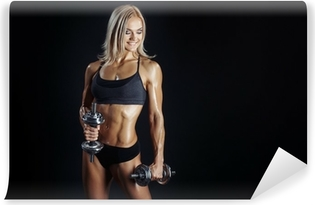 Athletic young woman doing a fitness workout with dumbbels on bl Vinyl Wall Mural
