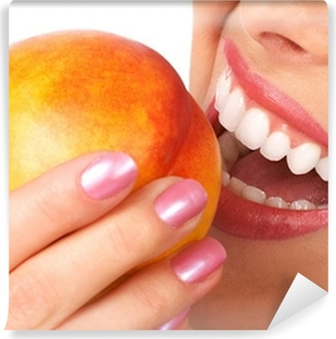Beautiful young woman eating a peach. Isolated over white. Vinyl Wall Mural