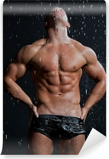 Muscle wet sexy young naked man posing under the rain in studio Vinyl Wall Mural
