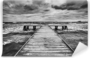 Old wooden jetty during storm on the sea. Dramatic sky Vinyl Wall Mural