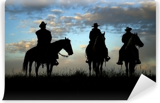 Three cowboys on horseback silhouetted against dawn sky Vinyl Wall Mural