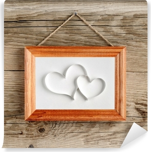 Two Hearts In Old Picture Frame Hanging On Wooden Wall Canvas Print