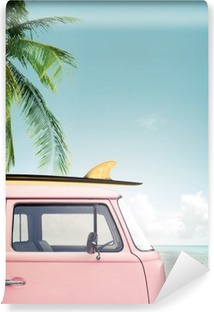 Vintage car parked on the tropical beach (seaside) with a surfboard on the roof Vinyl Wall Mural