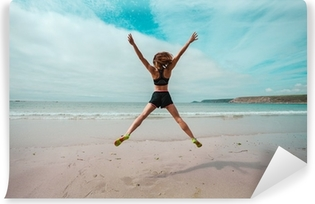 Young woman doing star jumps on the beach Vinyl Wall Mural