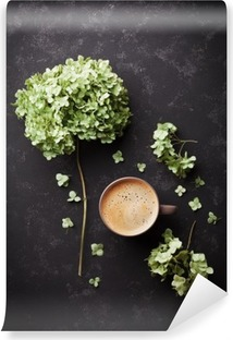 Composition with cup of coffee and dried flowers hydrangea on black vintage table from above, flat lay Washable Wall Mural