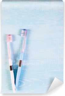 Two toothbrushes and chamomile flowers on a light background. The concept of natural cosmetics for health. You me. View from above Washable Wall Mural