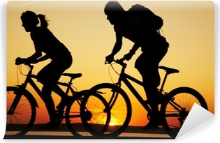 Young couple riding bicycles at sunset Washable Wall Mural