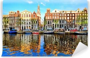 Zelfklevend Fotobehang Grachtenpanden van Amsterdam in de schemering met levendige reflecties