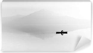 Zelfklevend Fotobehang Mist over het meer. Silhouet van de bergen op de achtergrond. De man drijft in een boot met een peddel. Zwart en wit