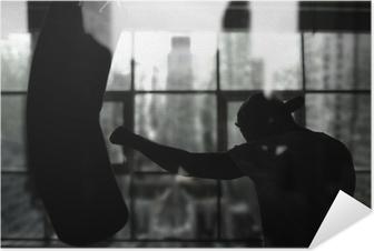 Zelfklevende Poster Boxer raakt een bokszak tegen het raam, training