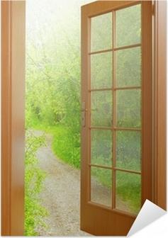 Zelfklevende Poster Open deur naar de vroege ochtend in de groene tuin.
