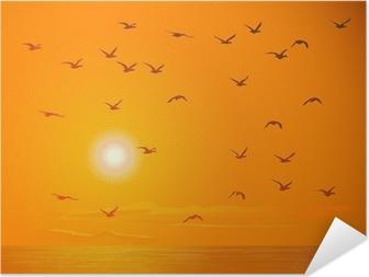 Zelfklevende Poster Vliegende vogels tegen oranje zonsondergang.