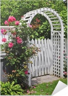 Zelfklevende Poster Wit prieel met rode bloeiende rozen in een tuin