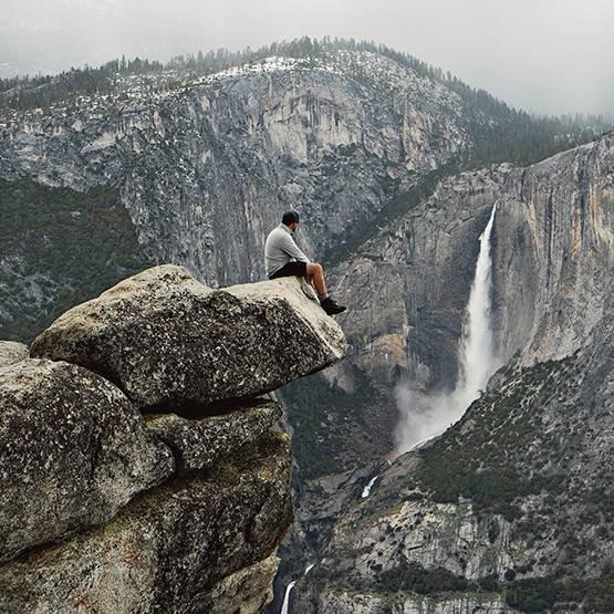Uomo seduto sulla roccia