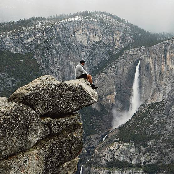 Adam kayalıkta oturuyor